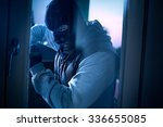 burglar with crowbar to break door to enter the house - stock photo