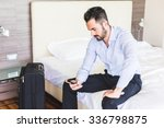 Stock photo businessman looking at smart phone in his hotel room he is sitting on the bed wearing black 336798875