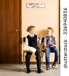 Small photo of Two schoolboys are sitting next to principal's office. They are twin, but they have different each other behavior and clothes. For creating this picture were used two image of one and the same boy.