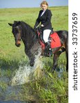 horsewoman and her horse /  spray water - stock photo