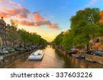 Stock photo tourist canal tour boat at sunset in one of the beautiful canals of amsterdam the netherlands 337603226