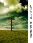 meadow with cloudy sky and religious cross - stock photo