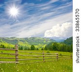 Fence in mountains meadow - stock photo
