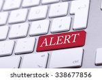 Small photo of Aluminium keyboard with alert word on it on red key. Danger and alert