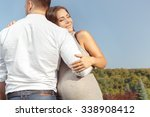 Small photo of That is what love looks like. Horizontal portrait of a husband hugging his beautiful pregnant wife