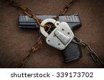 Small photo of Gun Control Concept - Pistol behind Lock and Chain