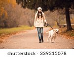 Stock photo portrait of a beautiful young woman with her dog while walking in the autumn park 339215078
