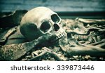 Small photo of Creepy human skull in an open grave surrounded by the bones of the skeleton in a macabre background for horror, Halloween or death themed concepts