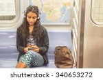 Small photo of Young asian woman sitting in a subway car and listening music with her smartphone - Pretty girl riding on a train and going to work