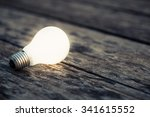 white light bulb glowing on the ... | Shutterstock . vector #341615552