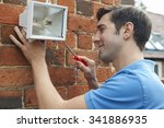 Man Fitting Security Light To...