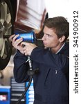 Small photo of Mechanic In Garage Using Air Hammer On Wheel