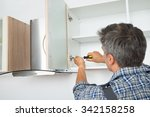 Stock photo rear view of serviceman fixing cabinet with screwdriver in kitchen 342158258