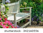white wood chair in the flowers