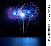 blue fireworks above water with ...