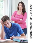 Small photo of Frustrated Mother Watching Teenage Son Doing Homework