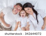 happy family lying on a bed... | Shutterstock . vector #342644072