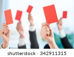 Small photo of Hands of business people showing red cards to condemn bad business practice