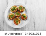 a plate with stuffed mushrooms... | Shutterstock . vector #343031015