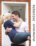 Small photo of Man Carrying Woman Over Threshold Of New Home