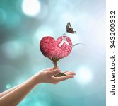Small photo of White ribbon on red love heart tree with butterfly on woman's hands on blurred abstract background of cyan blue sky: International Day for the Elimination of Violence against Women concept