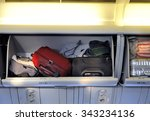 Carry-on luggage in overhead storage compartment on commercial airplane. - stock photo
