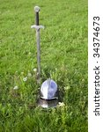 sword and helmet on the green grass - stock photo