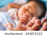 Small photo of Mother with her newborn baby care hands
