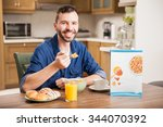 Small photo of Portrait of a good looking young man eating cereal and smiling at home. Cereal box included