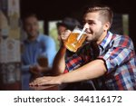 young men drinking beer in pub | Shutterstock . vector #344116172