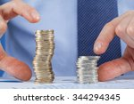 businessman comparing stacks of ... | Shutterstock . vector #344294345