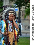 Small photo of SAINT-PETERSBURG, RUSSIA - JULY 18, 2014 - Peruvian street musician with pan flute talks on the phone. St-Petersburg, Russia