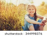 Small photo of happy child girl in jeans overall playing on sunny field, summer outdoor lifestyle, cozy mood