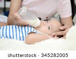 adorable baby drinking milk on... | Shutterstock . vector #345282005