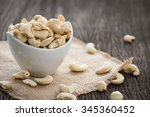 raw cashew nuts in white... | Shutterstock . vector #345360452