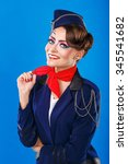 Small photo of Stewardess with face art corrects neckerchief. Young attractive girl in a blue suit flight attendants. Airfreight.