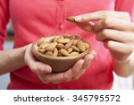woman eating healthy snack of... | Shutterstock . vector #345795572
