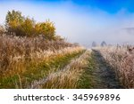 road through hillside with frozen grass meadow in mountains in morning fog at sunrise - stock photo