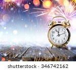 Small photo of Midnight Celebration - Clock On Snowy Table With Fireworks