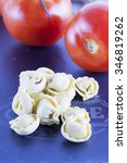 Small photo of Agnolotti and tomatoes over black stone, vertical image
