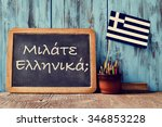 Small photo of a chalkboard with the question question do you speak greek? written in greek, a pot with pencils, an eraser and the flag of Greece, on a wooden desk