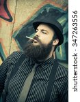 Small photo of Snazzy bearded man smokes a cigarette on a city street