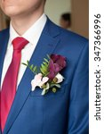 Small photo of the groom in a blue suit and a claret buttonhole