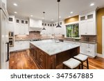 Stock photo large kitchen interior with island sink white cabinets pendant lights and hardwood floors in 347567885