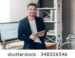 Small photo of Confident business expert. Confident young man holding digital tablet and smiling while leaning at the deck in office