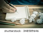 Stock photo hand with pen on empty note book with crumpled papers around 348589646