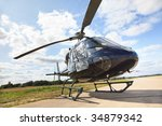 Black helicopter standing on landing strip in airfield. Low angle view with nice cloud reflection. - stock photo