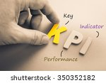 Small photo of Hand arrange wood letters as KPI acronym (Key Performance Indicator)