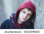 Stock photo dramatic portrait of a little homeless boy poverty city street 351009065