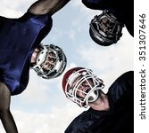 Small photo of American football huddle against blue sky with white clouds